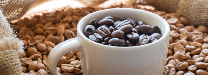 dettaglio di una tazzina colma di chicchi di caffè