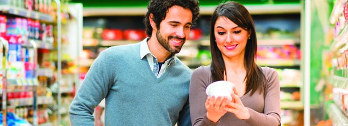 una coppia di persone al supermercato che leggono un'etichetta alimentare su un prodotto