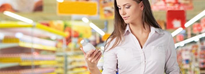 ragazza che legge l'etichetta di un prodotto in un supermercato