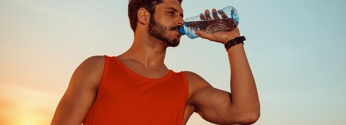 uomo sportivo che beve acqua per reintegrare i minerali persi