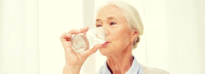 persona anziana che beve un bicchiere di acqua