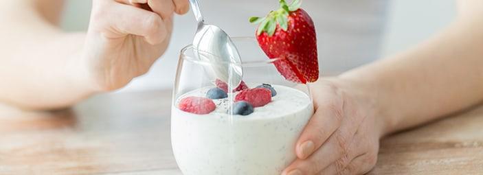 dettaglio di un bicchiere di yogurt con pezzi di frutta